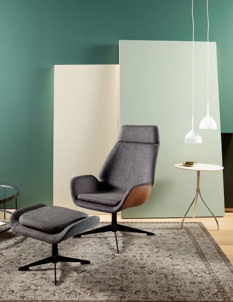 modern armchair with footrest against blue wall with side table and two white hanging lights