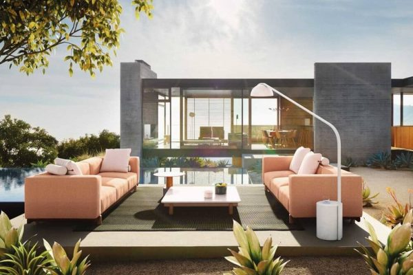 outdoor commercial furniture by pool next to building