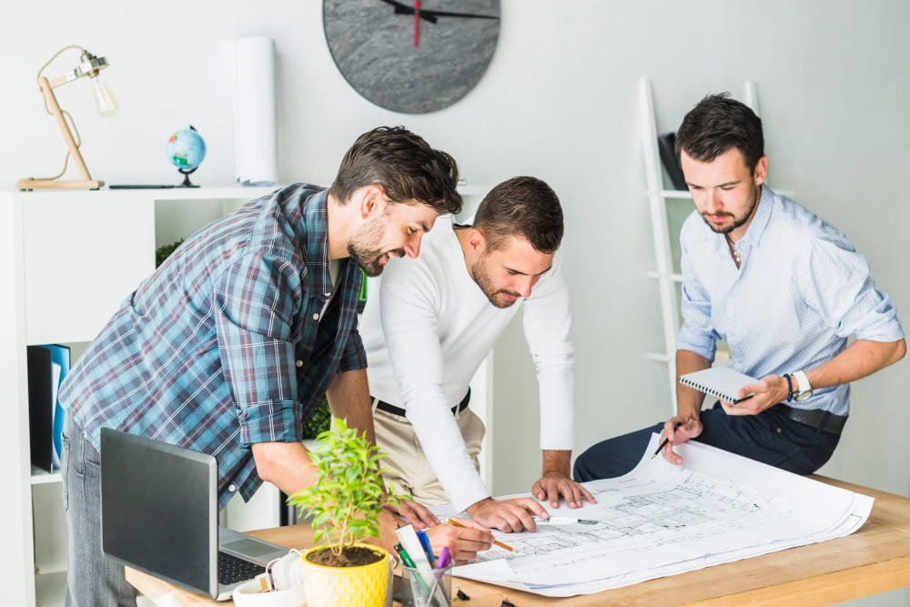 three office design and furniture looking at design plans