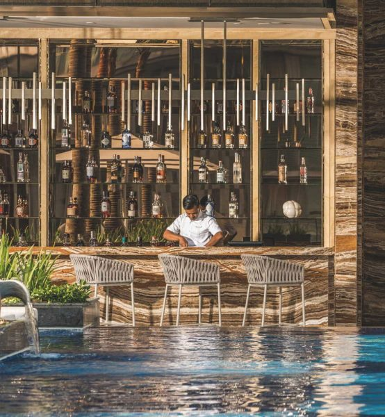 bar by a pool attended by a bartender featuring three modern bar stools